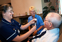 Discharged elderly patient is visited in his home by two district nurses to show him how to use his medication Bradford Yorkshire UK