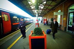Staff and passengers on Grantham Station railway platform as a train waits to depart, Lincolnshire, England, United Kingdom.