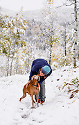 SHOT 10/1/17 4:03:18 PM - Vesta Lingvyte of Denver, Co. pauses while hiking along Buffalo Pass to kiss Tanner, a 13 year-old male Vizsla, in Steamboat Springs, Colorado. An unexpected early season snowfall covered the changing aspen leaves in a fresh coat of snow. Populus tremuloides is a deciduous tree native to cooler areas of North America, one of several species referred to by the common name aspen. It is commonly called quaking aspen,trembling aspen or American aspen. The trees have tall trunks, up to 25 meters (82 feet) tall, with smooth pale bark, scarred with black. The glossy green leaves, dull beneath, become golden to yellow, rarely red, in autumn. The species often propagates through its roots to form large groves originating from a shared system of rhizomes. (Photo by Marc Piscotty / © 2017)