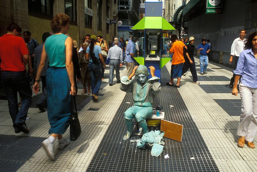 """ARGENTINA/ BUENOS AIRES/ La peatonal calle Florida en el centro de la ciudad. En la imagen, un mimo se prepara para ser estatua viviente...ARGENTINA/ BUENOS AIRES/ Florida pedestrian street at downtown. In the image, an actor prepares to perform as a """"street living statue""""."""