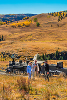 Passengers learn about the The Cumbres & Toltec Scenic Railroad from a railroad employee during a stop at Osier, Colorado. The train is pulled by a steam locomotive on the 64 mile run between Chama, New Mexico and Antonito, Colorado. The railroad is the highest and longest narrow gauge steam railroad in the United States with a track length of 64 miles. The train traverses the border between Colorado and New Mexico, crossing back and forth between the two states 11 times. The narrow gauge track is 3 feet wide. It runs over 10,015 ft (3,053 m) Cumbres Pass.