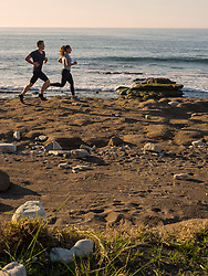 Man and woman running on single trail on coast of Azkorri beach