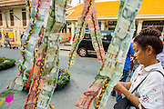 """09 FEBRUARY 2013 - BANGKOK, THAILAND:  A woman makes an offering of Thai Baht for Chinese New Year at Wat Traimit in Chinatown in Bangkok. Bangkok has a large Chinese emigrant population, most of whom settled in Thailand in the 18th and 19th centuries. Chinese, or Lunar, New Year is celebrated with fireworks and parades in Chinese communities throughout Thailand. The coming year will be the """"Year of the Snake"""" in the Chinese zodiac.   PHOTO BY JACK KURTZ"""