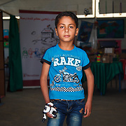 """Muhanad, 7, and his family left Daraa, Syria two years ago for the safety of Jordan. He's holding a birthday gift from his grandfather, Muhamed. The toy reminds him of his grandfather, """"who is now in heaven.""""<br /> <br /> Muhanad is at his school, in one of the Mercy Corps extra curicular activity rooms where he participates in activities like drawing, painting, and games. Zaatari camp for Syrian refugees, Jordan, May 2015.<br /> <br /> Muhanad and his family have made their way to Germany since this photo was taken."""