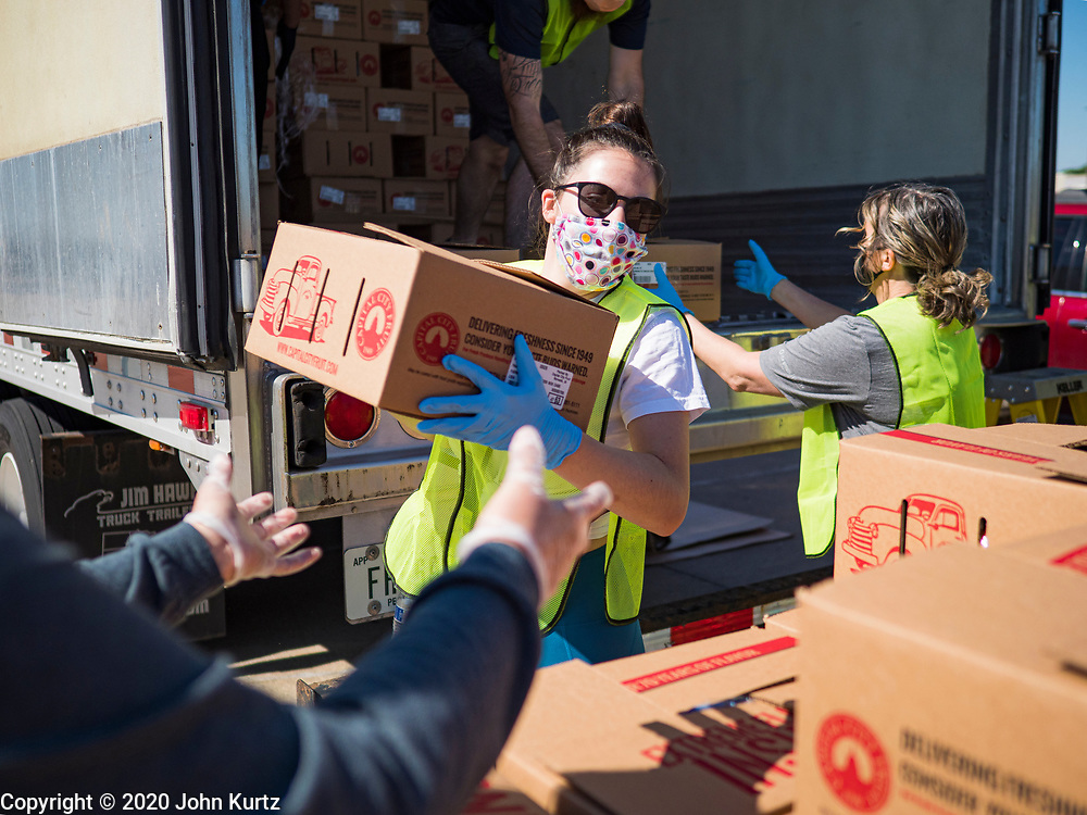 29 MAY 2020 - DES MOINES, IOWA: ELLA SUNDSPROM, a volunteer, stacks boxes of produce during a produce distribution in a mall parking lot in Des Moines. The Des Moines Area Religious Council (DMARC) and Capitol City Fruit from Norwalk, IA, gave away 1,800 boxes of fresh produce with a mix of vegetables and fruit. The boxes contain enough produce to feed a family of four for a week. The produce was provided by the USDA Farmers to a Families food program. Because of the COVID-19 pandemic, the unemployment rate in Iowa hit 10.2% in May, the highest unemployment rate ever recorded in Iowa and food insecurity in Iowa is impacting communities throughout the state.          PHOTO BY JACK KURTZ
