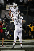 Oakland Raiders offensive tackle Vadal Alexander (74) lifts Oakland Raiders running back DeAndre Washington (33) high in the air in celebration after Washington runs for a 4 yard touchdown on a third quarter play good for a 21-20 Raiders lead during the 2017 NFL week 7 regular season football game against the against the Kansas City Chiefs, Thursday, Oct. 19, 2017 in Oakland, Calif. The Raiders won the game 31-30. (©Paul Anthony Spinelli)
