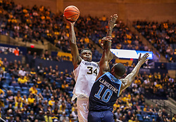 Dec 1, 2019; Morgantown, WV, USA; West Virginia Mountaineers forward Oscar Tshiebwe (34) shoots over Rhode Island Rams forward Cyril Langevine (10) during the second half at WVU Coliseum. Mandatory Credit: Ben Queen-USA TODAY Sports