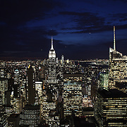 A vertical view of Manhattan, New York, at night time from the Top of the Rock, the observatory deck at Rockefeller Center showing the Empire State Building, Manhattan, New York, USA.  Photo Tim Clayton