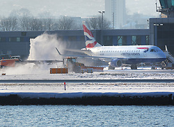 © Licensed to London News Pictures, 28/02/2018. London, UK. A British Airways passenger plane gets de-iced at London City Airport in sub zero temperatures after an overnight snow storm caused travel chaos across the capital . Photo credit: Steve Poston/LNP