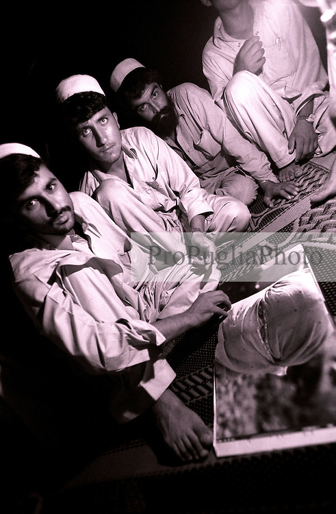 03 September 2005..Afghan students look at a picture of a woman displayed in a photographic book on Kashmir