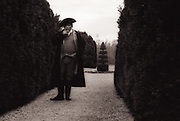 A man dressed in Colonial era clothing smokes a cigar while standing in a garden full of tall shrubs.