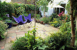 View of patio and folding chairs from rear of small town garden