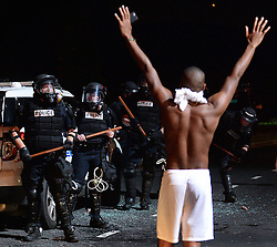 A protestor approaches CMPD officers with his arms up on Old Concord Rd. on Tuesday night, Sept. 20, 2016 in Charlotte, N.C. The protest began on Old Concord Road at Bonnie Lane, where a Charlotte-Mecklenburg police officer fatally shot a man in the parking lot of The Village at College Downs apartment complex Tuesday afternoon. The man who died was identified late Tuesday as Keith Scott, 43, and the officer who fired the fatal shot was CMPD Officer Brentley Vinson. Photo by Jeff Siner/Charlotte Observer/TNS/ABACAPRESS.COM
