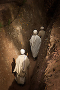 Priests walking down towards St George's Church, Lalibela. Ethiopia, Horn of Africa