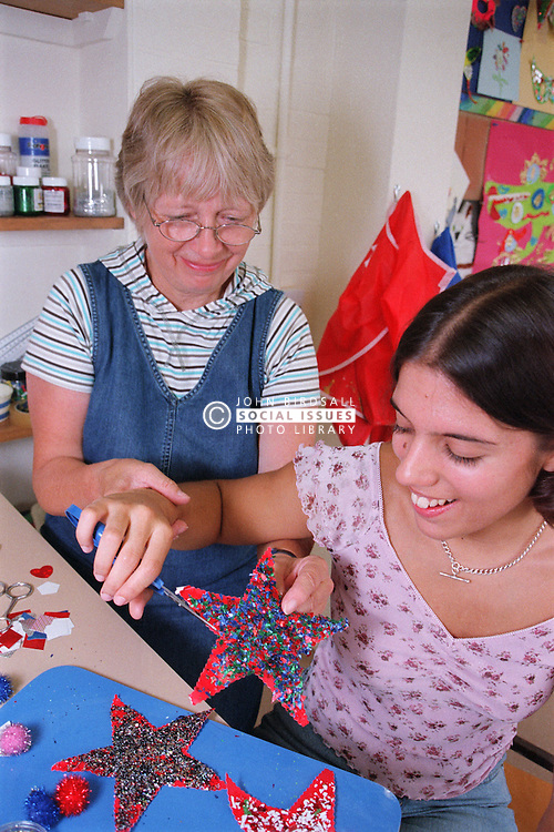 Carer assisting teenage girl to use self opening scissors in residential respite care home,