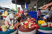 25 OCTOBER 2012 - PATTANI, PATTANI, THAILAND: A Muslim sells flower garlands used in Buddhist religious rituals to Buddhists in the market in Pattani, Thailand. Despite religious conflict Buddhists and Muslim in Pattani, there is still a lot of interaction between the two communities.     PHOTO BY JACK KURTZ