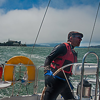 A sailor navigates through wind-chopped water in San Francisco Bay, California. Behind him is the abandoned prison on Alcatraz Island.