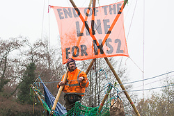Dan Hooper, widely known as Swampy during the 1990s, looks out from a basket suspended from a bamboo tripod positioned in the river Colne on 8th December 2020 in Denham, United Kingdom. The climate and roads activist had occupied the tripod the previous day in order to delay the building of a bridge as part of works for the controversial HS2 high-speed rail link and a large security operation involving officers from at least three police forces, National Eviction Team enforcement agents and HS2 security guards was put in place to facilitate his removal.