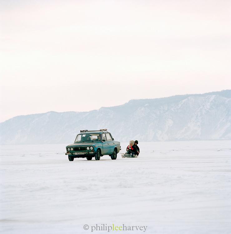 Sledging behind a car on a frozen Lake Baikal, Siberia, Russia
