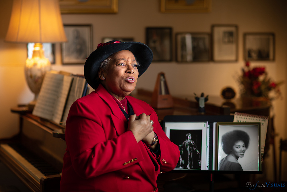 """Elvira Green sings beside her antique piano in her Greensboro home. Wearing one of her favorite hats  hat that is not too """"churchy.""""<br /> <br /> Elvira Green has had a prolific career as an opera singer.  She went from the Dudley High School choir to the halls of the Metropolitan Opera in New York. She was one of the few African-American women to break into a permanent spot at the Met during the 1970s as a mezzo-soprano. She performed her signature role as Maria in the opera """"Porgy and Bess."""" <br /> <br /> Photographed, Wednesday, January 16, 2019, in Greensboro, N.C. JERRY WOLFORD and SCOTT MUTHERSBAUGH / Perfecta Visuals"""