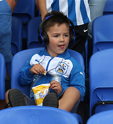 12 August 2017 London : Premier League Football : Crystal Palace v Huddersfield Town:  a young Town fan eats crisps while wearing his headphones.<br /> Photo: Mark Leech