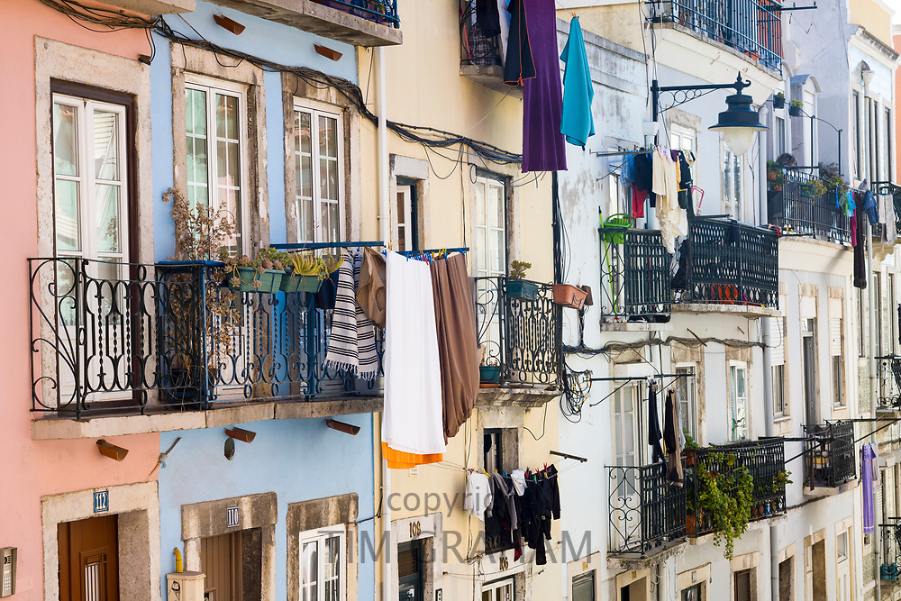 Typical Portugese steep street scene, laundry hanging to dry on washing lines and balconies in Lisbon, Portugal