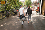 In Utrecht lopen twee jongens met visspullen over de Oudegracht.<br /> <br /> In Utrecht two boys are walking with fishing equipment.