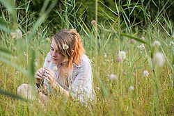 Young woman sitting on meadow and smelling a flower, Bavaria, Germany