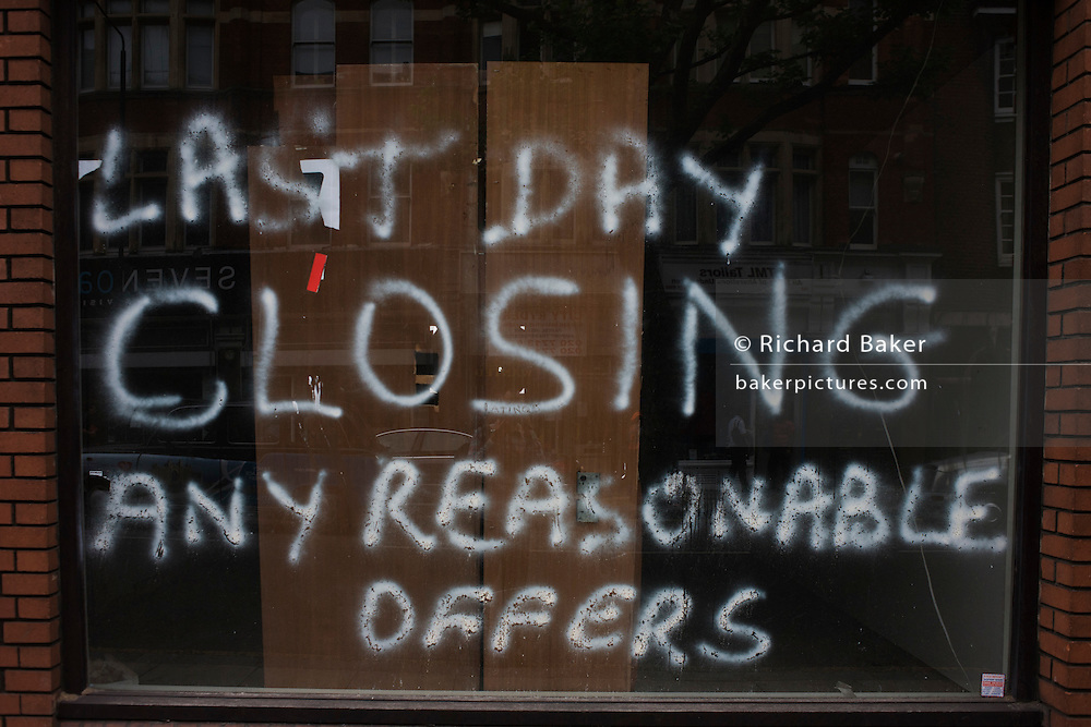Sprayed writing on a closed recession business window.