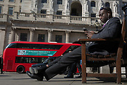 A businessman checks his messages opposite the Bank of England on Threadneedle Street in the City of London, the capitals financial district also known as the Square Mile, on 6th April 2017, in London, England.