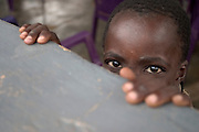 Young boy peeking from behind a wall in Aflao, Ghana