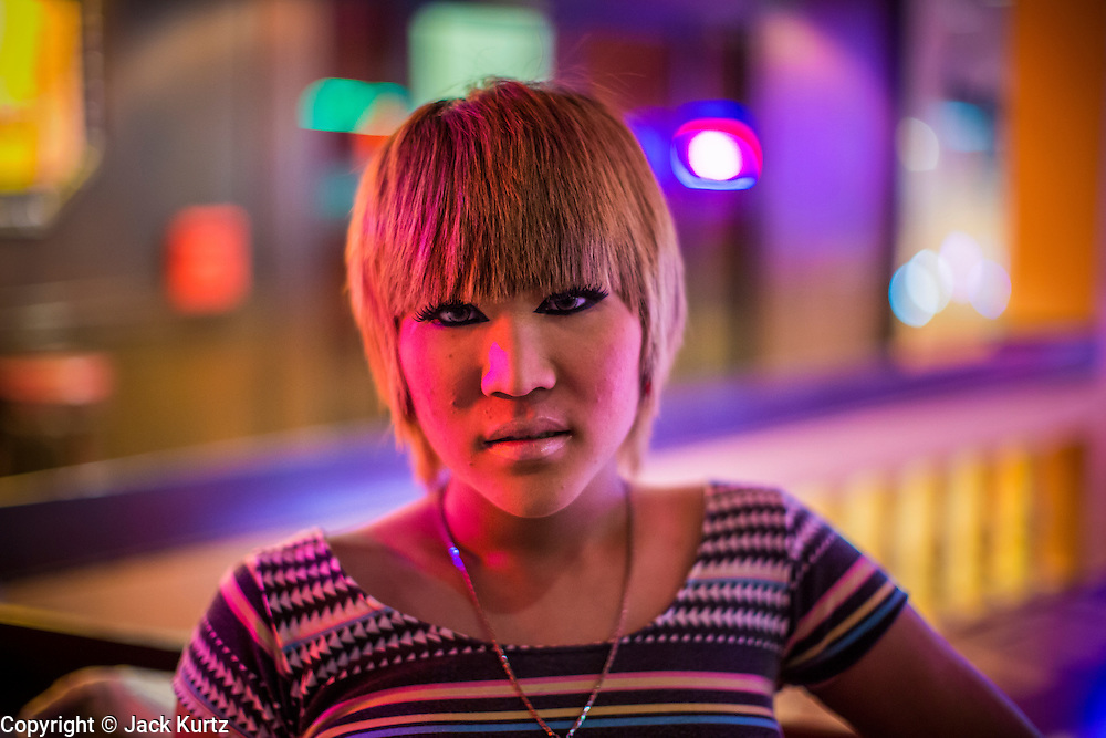 """18 JANUARY 2013 - BANGKOK, THAILAND: A transgendered sex worker waits for customers in the Nana Entertainment District in Bangkok. Prostitution in Thailand is technically illegal, although in practice it is tolerated and partly regulated. Prostitution is practiced openly throughout the country. The number of prostitutes is difficult to determine, estimates vary widely. Since the Vietnam War, Thailand has gained international notoriety among travelers from many countries as a sex tourism destination. One estimate published in 2003 placed the trade at US$ 4.3 billion per year or about three percent of the Thai economy. It has been suggested that at least 10% of tourist dollars may be spent on the sex trade. According to a 2001 report by the World Health Organisation: """"There are between 150,000 and 200,000 sex workers (in Thailand).""""          PHOTO BY JACK KURTZ"""