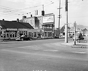 Ackroyd 02095-5. looking south–west from corner of Vancouver showing Broadway, and curve in road to bridge. March 28, 1950. The large building on the left with the Plymouth billboard was the Dude Ranch. Portland, Oregon.