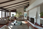Interior; living room of a rustic house; divans and fireplace