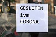 Nederland, Nijmegen, 30-4-2020  Op het raam van een winkel hangt de mededeling dat ze gesloten zijn vanwege de corona uitbraak .Foto: Flip Franssen
