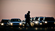 Photo Randy Vanderveen, © 2007 all rights reserved.Grande Prairie, Alberta.A pedestrian crosses the road in front of traffic silhouetted against the headlights and the pre-dawn sky.