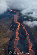 Aerial view of Kilauea Volcano east rift zone erupting hot lava from Fissure 8 in Leilani Estates subdivision near the town of Pahoa. The lava drains downhill as an incandescent river to Kapoho, Puna District, Hawaii Island ( the Big Island ), Hawaiian Islands, U.S.A. Toxic fumes from the lava have killed most of the vegetation on the left side of the picture.
