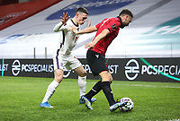 TIRANA, ALBANIA - MARCH 28: Keidi Bare of Albania shields the ball from Phil Foden of England during the FIFA World Cup 2022 Qatar qualifying match between Albania and England at the Qemal Stafa Stadium on March 28, 2021 in Tirana, Albania. Sporting stadiums around Europe remain under strict restrictions due to the Coronavirus Pandemic as Government social distancing laws prohibit fans inside venues resulting in games being played behind closed doors (Photo by MB Media)