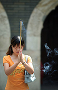 A woman prays at the Tanzhesi temple. Situated in the Western Hills, this Buddhist temple lies 45km west of Beijing. The temple name means 'Dragon Pool and Mulberry Tree Temple', due to its proximity to the Dragon Pool and the trees growing in the surrounding hills.....