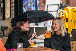 © Licensed to London News Pictures. 23/09/2020. London, UK. Friends, Anna Haigh (Left) and Megan Thompson both 30 from Whitechapel in East London enjoy a pint or two in Soho despite the rain on the last evening before the 10pm pub curfew comes in to force with the restrictions possibly lasting up to six months. The Prime Minister Boris Johnson addressed the Nation yesterday with further tougher Covid restrictions including early closing of pubs by 10pm and increased fines for not wearing a face mask as a spike in coronavirus cases continues throughout the UK. Photo credit: Alex Lentati/LNP