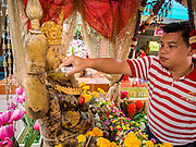 31 AUGUST 2014 - SARIKA, NAKHON NAYOK, THAILAND: A man pours holy oil on a statue of Ganesh at Shri Utthayan Ganesha Temple in Sarika, Nakhon Nayok. Ganesh Chaturthi, also known as Vinayaka Chaturthi, is a Hindu festival dedicated to Lord Ganesh. It is a 10-day festival marking the birthday of Ganesh, who is widely worshiped for his auspicious beginnings. Ganesh is the patron of arts and sciences, the deity of intellect and wisdom -- identified by his elephant head. The holiday is celebrated for 10 days, in 2014, most Hindu temples will submerge their Ganesh shrines and deities on September 7. Wat Utthaya Ganesh in Nakhon Nayok province, is a Buddhist temple that venerates Ganesh, who is popular with Thai Buddhists. The temple draws both Buddhists and Hindus and celebrates the Ganesh holiday a week ahead of most other places.    PHOTO BY JACK KURTZ