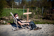 """Portrait of a man with a mask sitting on a beach chair on a place called """"Corona beach"""" in times of social distancing related to the spreading of the corona virus."""