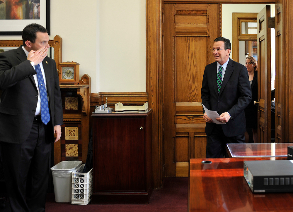 Connecticut Gov. Dannel P. Malloy, right, is saluted by a staff member as he approaches his first news conference as governor in his office at the Capitol in Hartford, Conn., Thursday, Jan. 6, 2011.  (AP Photo/Jessica Hill)