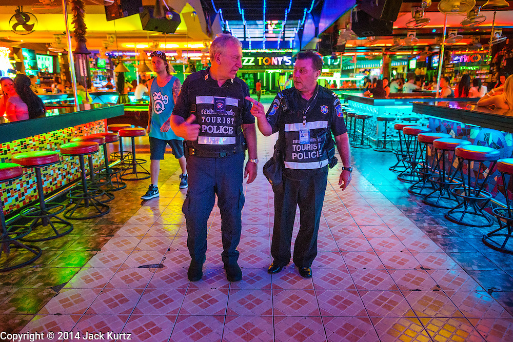 """26 SEPTEMBER 2014 - PATTAYA, CHONBURI, THAILAND: Members of the Foreign Tourist Police Assistants (FTPA) patrol Walking Street in Pataya. The FTPA assist local police in dealing with foreign tourists but don't have arrest powers. Pataya, a beach resort about two hours from Bangkok, has wrestled with a reputation of having a high crime rate and being a haven for sex tourism. After the coup in May, the military government cracked down on other Thai beach resorts, notably Phuket and Hua Hin, putting military officers in charge of law enforcement and cleaning up unlicensed businesses that encroached on beaches. Pattaya city officials have launched their own crackdown and clean up in order to prevent a military crackdown. City officials have vowed to remake Pattaya as a """"family friendly"""" destination. City police and tourist police now patrol """"Walking Street,"""" Pattaya's notorious red light district, and officials are cracking down on unlicensed businesses on the beach.     PHOTO BY JACK KURTZ"""