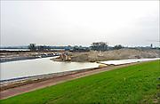 Nederland, Nijmegen, 26-11-2014 Aan de overkant van de Waal bij Lent wordt druk gewerkt aan het creeren van een nevengeul in de rivier om bij hoogwater een betere waterafvoer te hebben. Het is een omvangrijk project waarbij onder meer de pijlers van het spoorviaduct een bredere basis moeten krijgen omdat die straks in de loop van het water staan. Ook de n325 die vanaf de Waalbrug naar Arnhem loopt moet over 400 meter opnieuw worden aangelegd omdat het talud vervangen wordt door pijlers. De weg wordt via een bypass omgeleid. Het dorp veurlent komt op een kunstmatig eiland te liggen met twee bruggen als ontsluiting. Een voetgangersbrug en de andere voor normaal verkeer. Inmiddels begint de nieuwe kade aan de noordkant van deze geul vorm te krijgen. Ruimte voor de rivier, water, waal. Op de foto:  In de nieuwe dijk wordt een drempel gebouwd die stapsgewijs water doorlaat en bij hoogwater overloopt. Measures taken by Nijmegen to give the river Waal, Rhine, more space to flow during highwater and to prevent the risk of flooding. Room for the river. Reducing the level, waterlevel. Foto: Flip Franssen/Hollandse Hoogte
