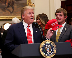 """U.S. President Donald Trump shows a hat that says """"Make County great again"""" before signing an Executive Order, to roll back the Obama administration's Waters of the United States rule, known as the Wotus, in the Roosevelt Room of the White House, February 28, 2017."""