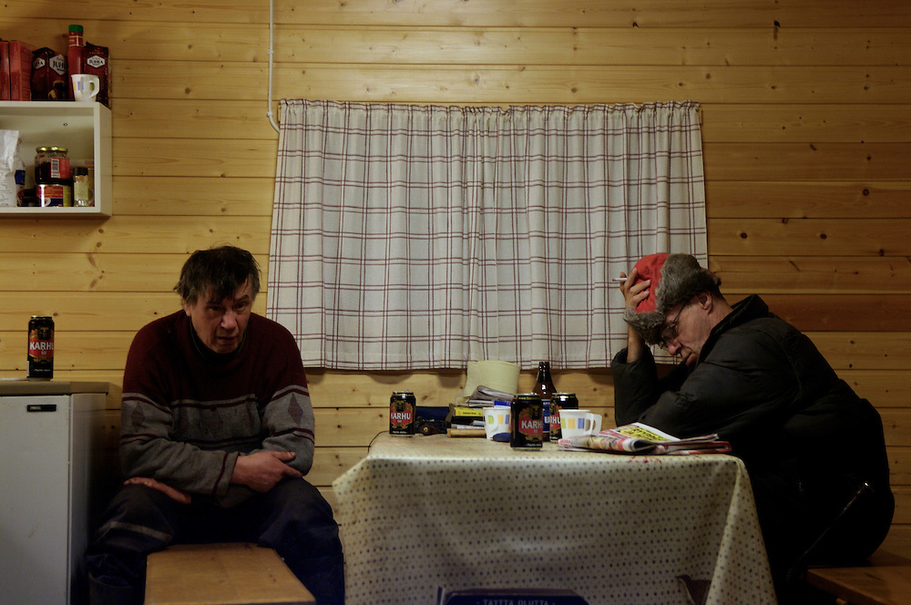 Hirvas Salmi, FINLAND.  Two herdsmen retreat to the warm of a cabin and share beer after struggling through a week of 12-16 hour days. Roundup weeks are notoriously relentless, requiring great exertion with very little time for recovery.  Alcoholism is endemic to Finland and even more pronounced in the Sami.