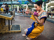 03 SEPTEMBER 2015 - BANGKOK, THAILAND: One of the Erawan Shrine dancers prays at Erawan Shrine Thursday. Repairs to Erawan Shrine were completed Thursday, Sept 3 after the shrine was bombed on August 17. Twenty people were killed in the bombing and more than 100 injured. The statue of the Four Faced Brahma in the shrine was damaged by shrapnel and a building at the shrine was damaged by debris.    PHOTO BY JACK KURTZ