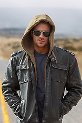 sexy man in sunglasses walking on a road