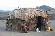 Africa, Tanzania, Samburu Maasai woman and baby in front of her hut an ethnic group of semi-nomadic people February 2006